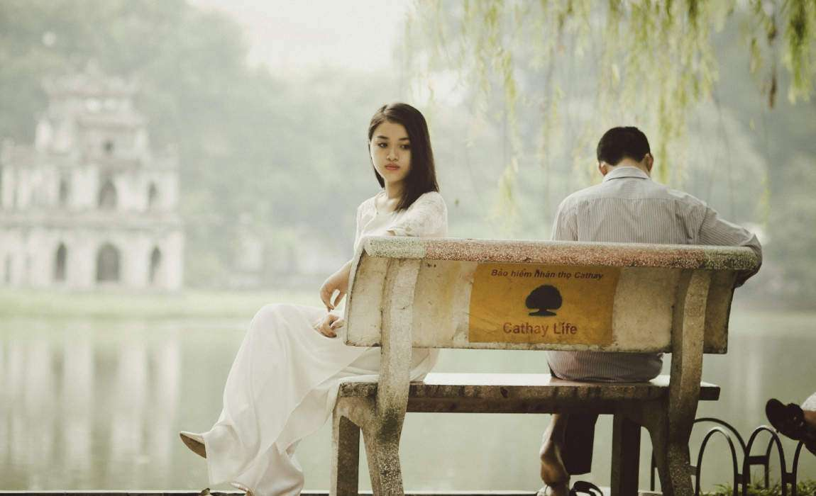 Man and woman sitting on bench after argument
